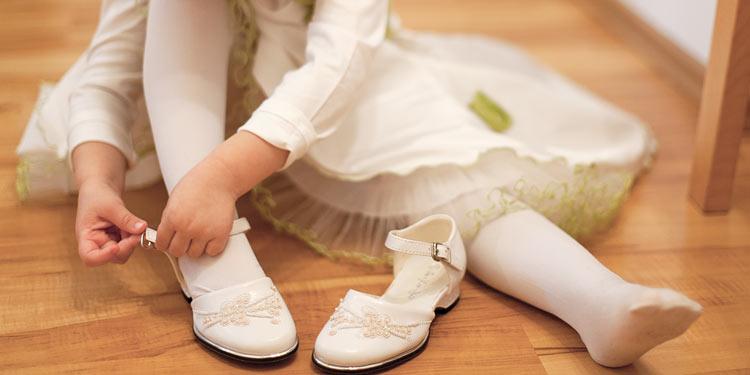 Blumenmädchen beim Schuhanziehen