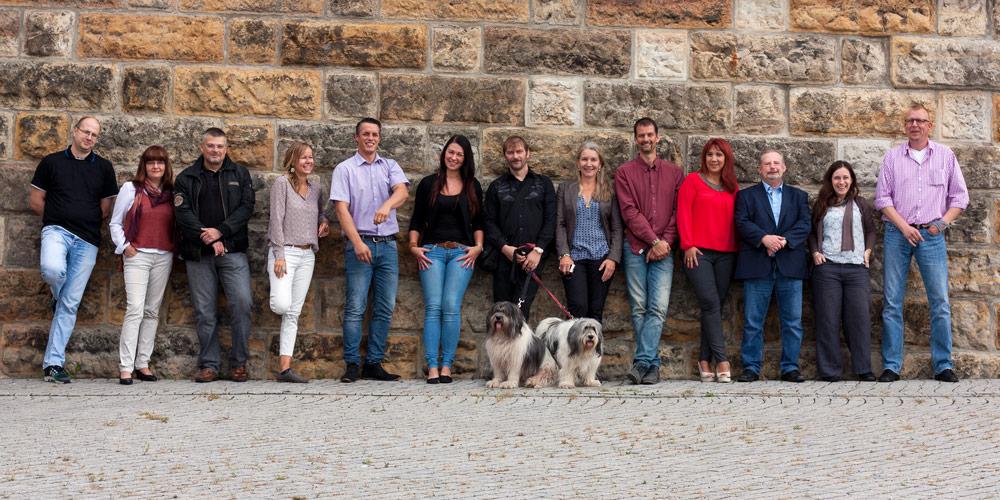 Mitarbeiter-Gruppenfoto vor einer Mauer