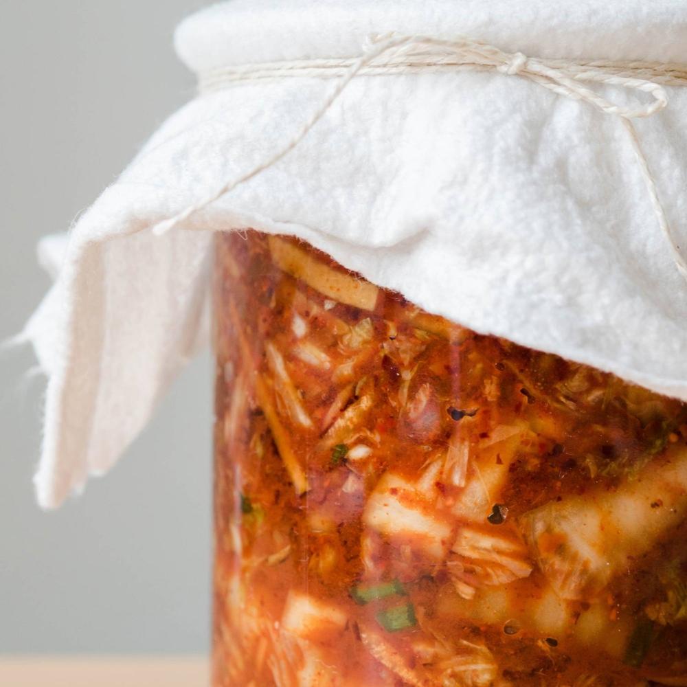 Kimchi-Gläser mit einem sauberen, luftdurchlässigen Tuch bedecken