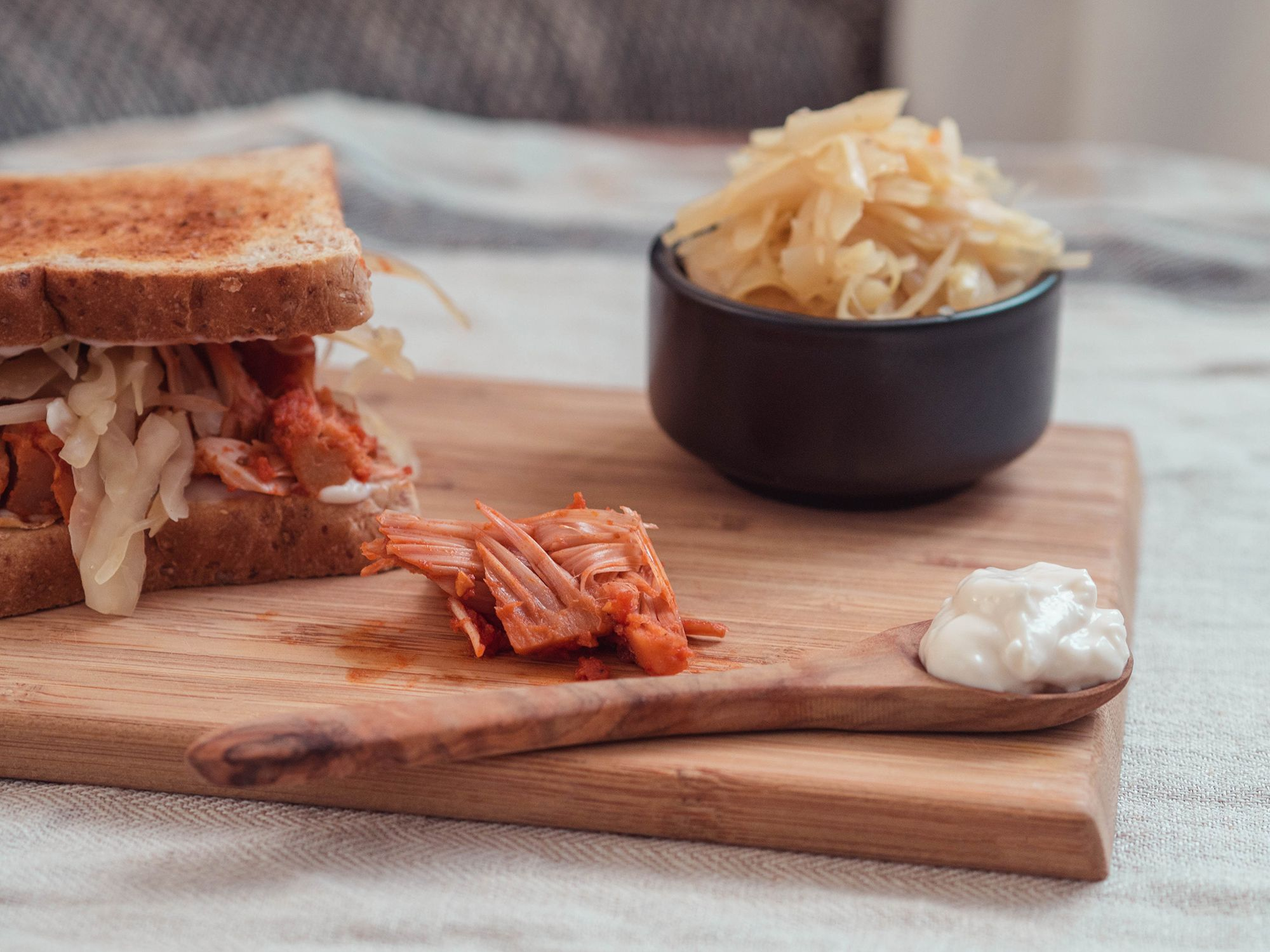 Selbstgemachtes Sauerkraut, Pulled Jackfruit und vegane Mayonnaise zwischen Toastbrot